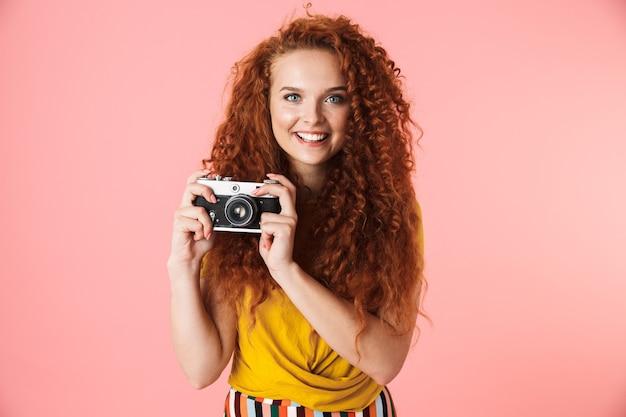 Portret van een aantrekkelijke vrolijke jonge vrouw met lang krullend rood haar die geïsoleerd staat en foto's maakt met een fotocamera