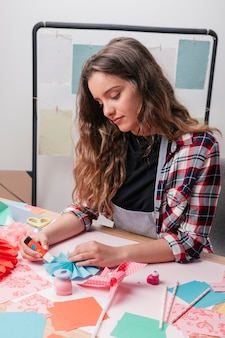 Portret van een aantrekkelijke vrouw die creatieve origamibemanningen maakt