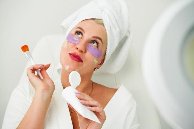 Portret van een aantrekkelijke vrouw die crème en make-upborstel in de hand houdt en een zijdezachte, vlekkeloze huid aanraakt
