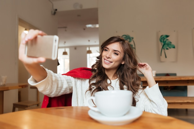 Portret van een aantrekkelijke vrouw die een selfie neemt