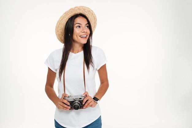 Portret van een aantrekkelijke vrouw die in hoed een camera houdt