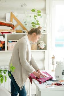 Portret van een aantrekkelijke vrouw die met een naaienpatroon werkt