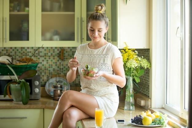 Portret van een aantrekkelijke vrouw die op een keuken tafel zit