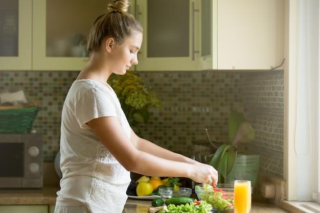 Portret van een aantrekkelijke vrouw die verse salade op de kitche maakt