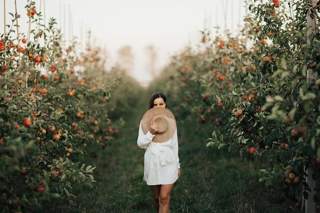 Portret van een aantrekkelijke vrouw in de appeltuin. een jonge en mooie vrouw in een witte jurk houdt een strooien hoed in haar hand.