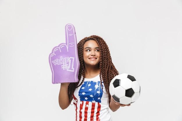 Portret van een aantrekkelijke vrouw met nummer één fanhandschoen en voetbal terwijl ze geïsoleerd tegen een witte muur staat