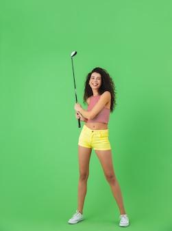 Portret van een aantrekkelijke vrouw van 20 in de zomer die een club draagt en golf speelt terwijl ze op een groene muur staat