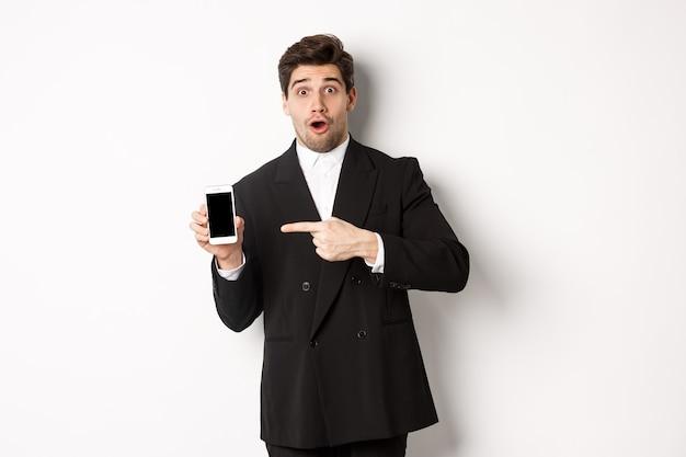 Portret van een aantrekkelijke zakenman in een zwart pak, die verrast kijkt en met de vinger naar het scherm van de smartphone wijst, staande op een witte achtergrond