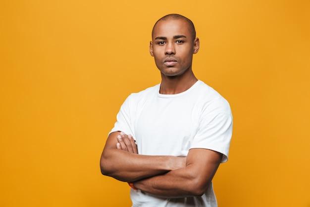 Portret van een aantrekkelijke, zelfverzekerde, casual jonge afrikaanse man die over een gele muur staat, met gevouwen armen