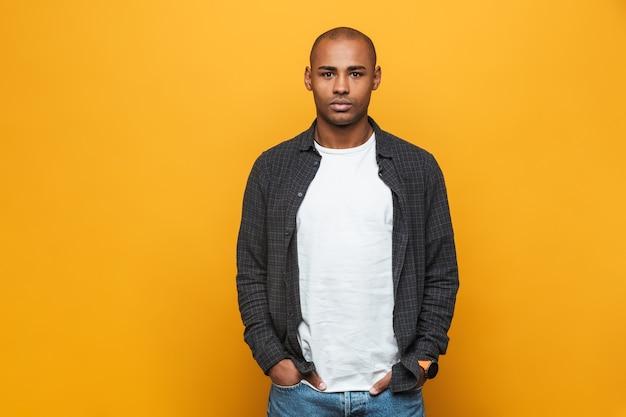 Portret van een aantrekkelijke zelfverzekerde casual jonge afrikaanse man die over een gele muur staat