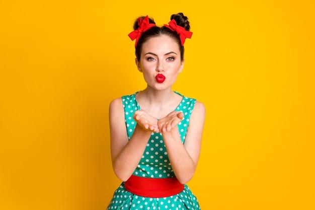 Portret van een aardig charmant lief meisje dat je luchtkus rode lippen stuurt, geïsoleerd over een levendige gele kleurachtergrond