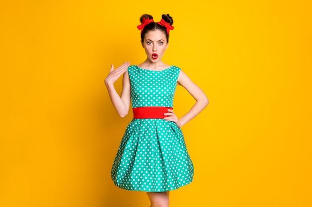 Portret van een aardig, charmant, verbaasd meisje met een gestippelde jurknieuwsreactie geïsoleerd over een levendige gele kleurachtergrond