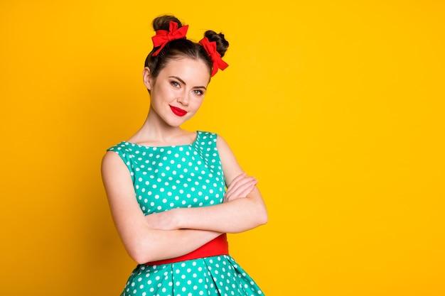 Portret van een aardig, glamoureus, vrolijk meisje met een gestippelde jurk gevouwen rammen geïsoleerd op een felgele achtergrond