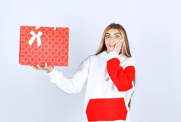 Portret van een aardig vrouwenmodel dat staat en een cadeauzakje laat zien