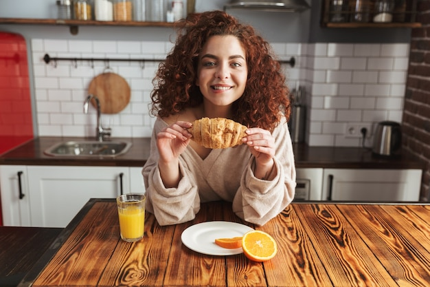 Portret van een aardige blanke vrouw die croissant eet en sinaasappelsap drinkt aan tafel in het keukeninterieur terwijl ze thuis ontbijt