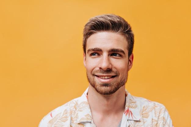 Portret van een aardige jonge man met stijlvol kapsel, blauwe ogen en baard in een licht, koel shirt dat wegkijkt en lacht op de oranje muur