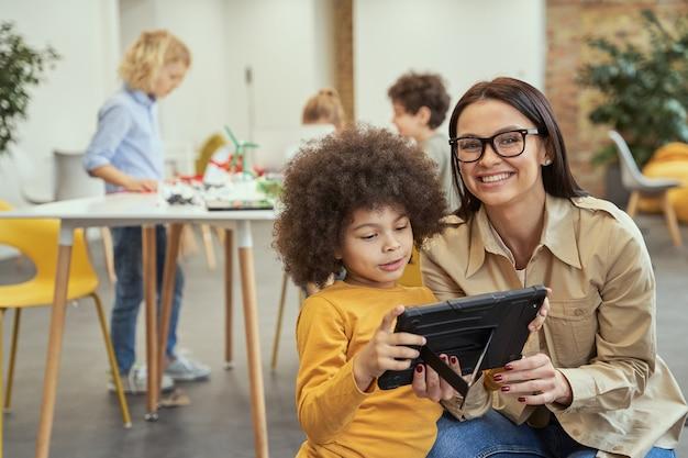 Portret van een aardige jonge vrouwelijke leraar die naar de camera glimlacht terwijl ze video op tablet-pc aan haar laat zien