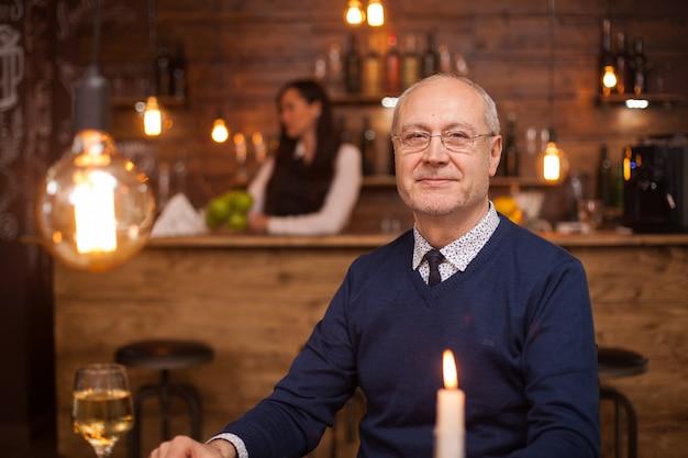 Portret van een aardige oude man die lacht naar de camera in een restaurant. man van in de zestig. volwassen mens.