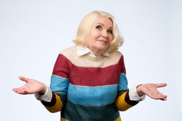 Portret van een aardige senior vrouw met een twijfelende gebaar.