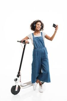 Portret van een aardige vrouw met een koptelefoon die selfie neemt