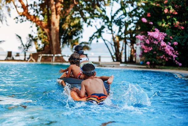 Portret van een actief kind dat een opblaasbare boot duwt, er zijn twee kleine vrienden van hem in een zwembad van een luxueus hotel.