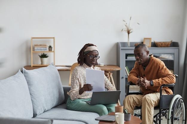 Portret van een afrikaans-amerikaans echtpaar met een gehandicapte man die samen vanuit huis werkt in een modern interieur, kopieer ruimte