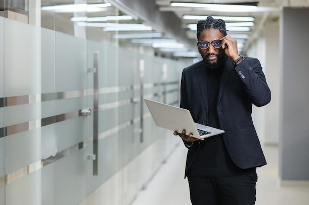 Portret van een afrikaanse amerikaan in een zwart pak op de achtergrond van de zwarte zakenman op kantoor met een laptop