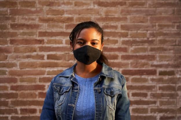 Portret van een afrikaanse amerikaanse zwarte die gezichtsmasker draagt die camera buiten bekijkt.