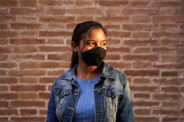 Portret van een afrikaanse amerikaanse zwarte die gezichtsmasker in openlucht draagt.