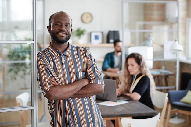Portret van een afrikaanse bebaarde zakenman die met gekruiste armen naar de camera glimlacht met zijn collega's die op kantoor op de achtergrond werken