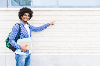 Portret van een Afrikaanse glimlachende mannelijke boeken van de studentenholding die in hand de vinger op witte geschilderde muur richten