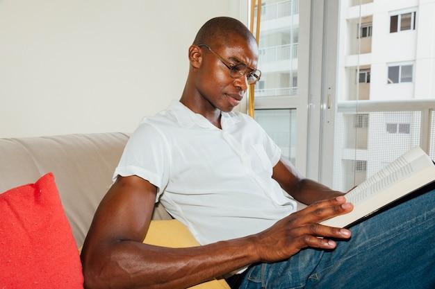Portret van een afrikaanse jonge man die het boek thuis leest