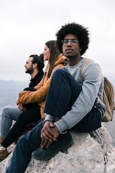 Portret van een afrikaanse jonge man zittend op de bergtop met zijn vrienden camera kijken