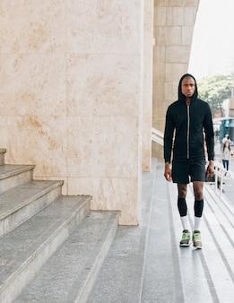 Portret van een afrikaanse jonge mannelijke atleet in zwarte hoodie die zich dichtbij de stappen bevindt