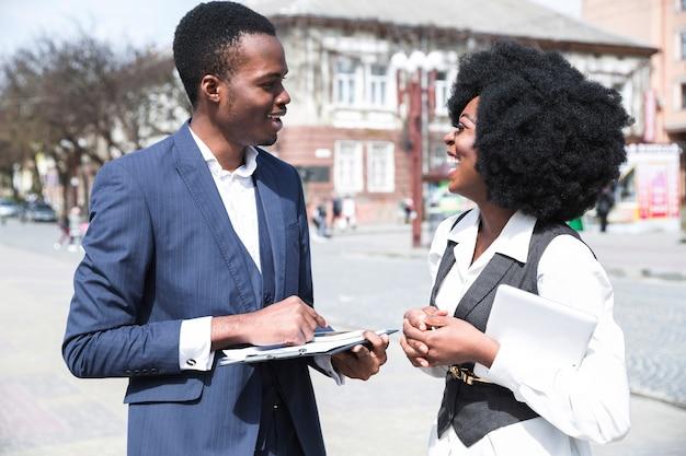 Portret van een afrikaanse jonge zakenman en onderneemster die aan elkaar in de stad spreken