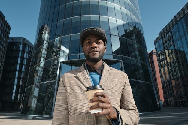 Portret van een afrikaanse jongeman die koffie drinkt uit een wegwerpbeker en naar de camera kijkt in de stad