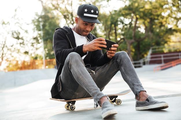 Portret van een afrikaanse kerel die op mobiele telefoon speelt
