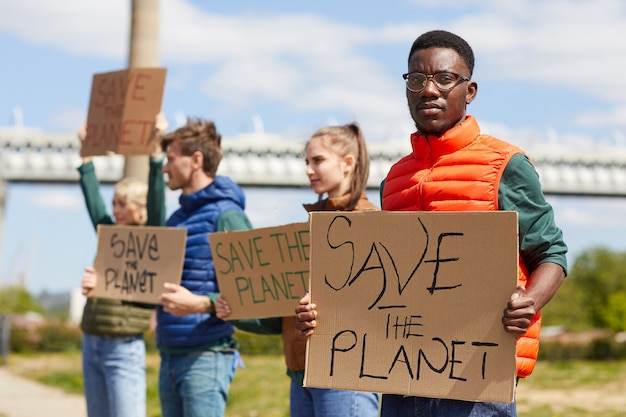 Portret van een afrikaanse man met plakkaat save the planet met zijn vrienden op de achtergrond