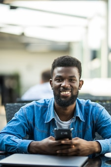 Portret van een afrikaanse man praten over de telefoon met laptop voor hem op tafel
