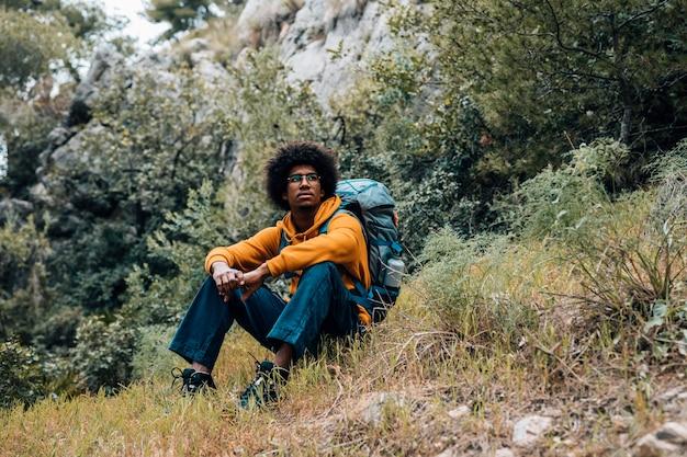 Portret van een afrikaanse mannelijke wandelaarzitting die in de berg rusten