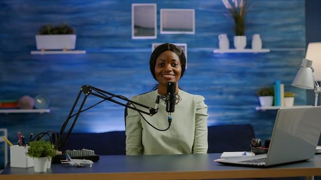 Portret van een afrikaanse vlogger die in een gezellige studio werkt, glimlachend naar de camera, klaar om een nieuwe podcastshow te starten. on-air online productie internetuitzending show host streaming webinhoud opnemen digitale blog