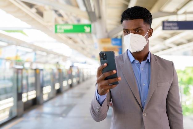 Portret van een afrikaanse zakenman op het perron van het treinstation die een gezichtsmasker draagt tijdens het gebruik van een mobiele telefoon