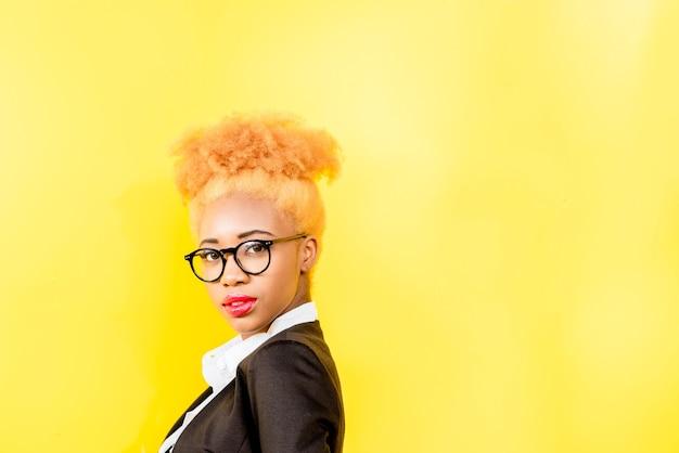 Portret van een afrikaanse zakenvrouw in een casual pak en een bril met een mooi kapsel op de gele muurachtergrond