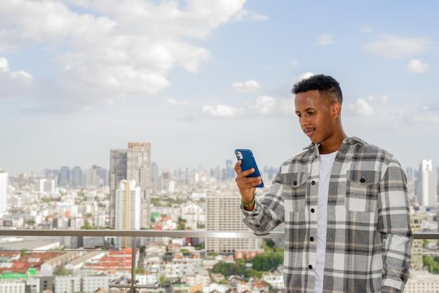 Portret van een afrikaanse zwarte man buiten in de stad op het dak tijdens de zomer met behulp van een horizontale opname van een mobiele telefoon