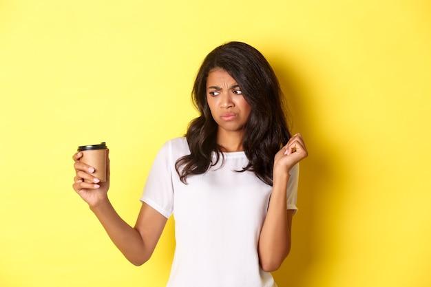 Portret van een afro-amerikaans meisje dat teleurgesteld kijkt naar de beker, houdt niet van slechte koffie die over schreeuwen staat...