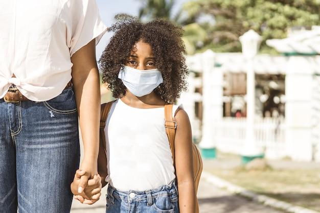 Portret van een afro-amerikaans meisje met een rugzak die een masker draagt, terug naar school en het nieuwe normaal