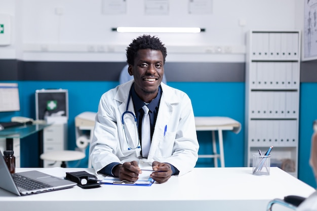 Portret van een afro-amerikaanse arts die aan een bureau zit