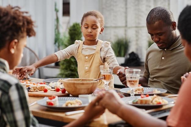 Portret van een afro-amerikaanse familie die elkaars hand vasthoudt tijdens het diner buitenshuis en bidt voor kopieerruimte