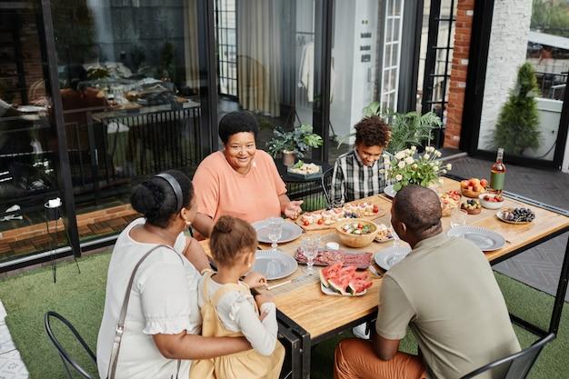 Portret van een afro-amerikaanse familie van meerdere generaties die buiten op het terras geniet van een diner...