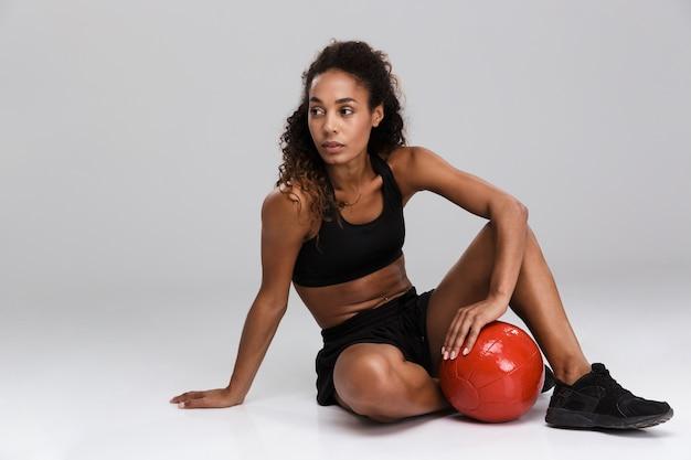 Portret van een afro-amerikaanse jonge fitte sportvrouw die oefeningen met zware bal doet die over grijze achtergrond worden geïsoleerd, zitten, wegkijken